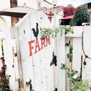 Rustic white gate with the Farm logo painted on front