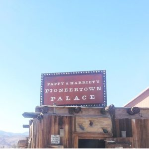 """Westen style sign saying """"Pappy & Harriet's Pioneertown Palace"""" in front of blue skies"""