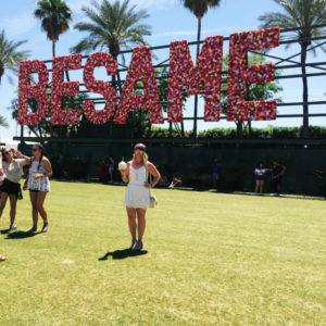 "Young woman in a white romper with a drink in hand in front of ""BESAME"" sign at Coachella Music Festival"