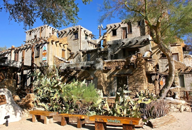 Cabot's Pueblo with desert foliage and wooden benches in foreground
