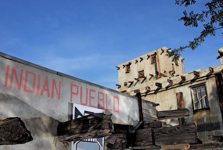 Artistic photograph of Cabot's Pueblo and the words 'Indian Pueblo' in red paint on side of building with clear, blue skies in background