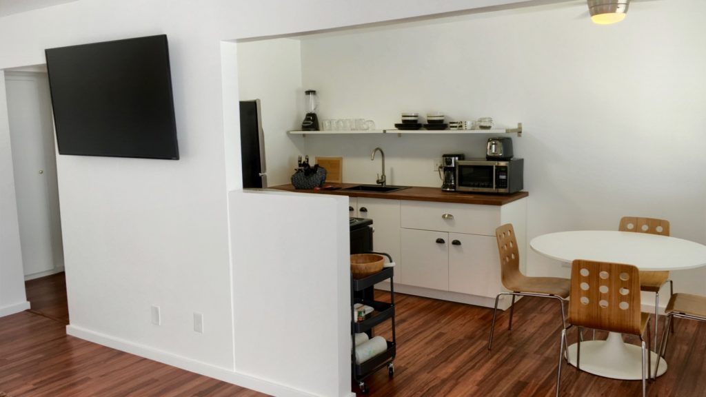 Modern, minimal and clean kitchen and dining space with white mid-century modern dining table and four modern, wooden chairs. Flat screen TV in living room seen to the left.
