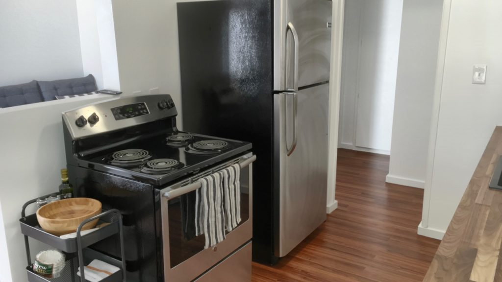 Black and stainless-steel oven/stove and refrigerator with small gray cart of kitchen supplied with the left