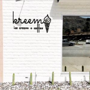 "White brick exterior with script font that reads ""Kreem Ice Cream + Coffee"""
