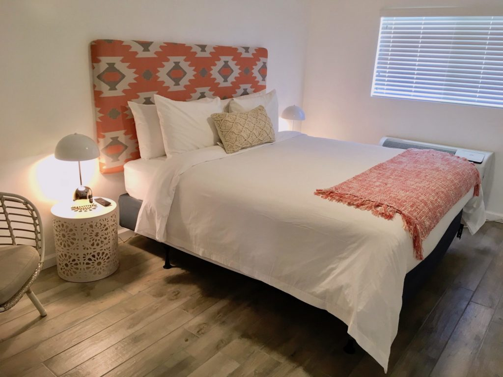 Clean, minimal bedroom with a king-sized bed with white bedding, one macrame accent pillow, and a salmon-colored throw blanket at the end of the bed. Pictured with a fun, gray and salmon headboard, and two bohemian bedside tables with white, modern lamps turned on.