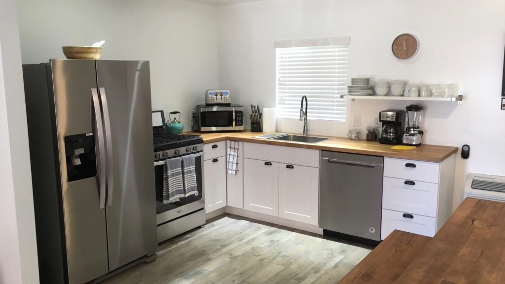 Large, modern, clean kitchen with stainless steel refrigerator, oven/stove, sink, and dishwasher. Various kitchen appliances (i.e., microwave, coffee pot, blender, toaster, kettle, etc.) seen on wooden counter tops with one simple open shelf above with white dishes stacked neatly on top