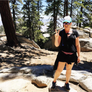 Young woman in baseball cap and sunglasses smiling and posing with peace sign on hike in the San Jacinto mountians