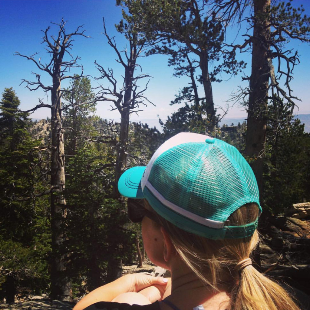 The back of young woman in baseball cap taking in the views of the San Jacinto mountain scenery