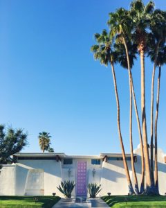 "Straight on photo of the ""That Pink Door"" house in Palm Springs, CA. A white, stucco exterior home with very tall, bright pink colored door and a tall cluster of palm trees to the right in the front yard"
