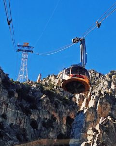 Photograph looking up at the Palm Springs Ariel Tramway's gold rotating tram car ascending the mountain with clear blue skies and ragged edges of the San Jacinto mountains in the background