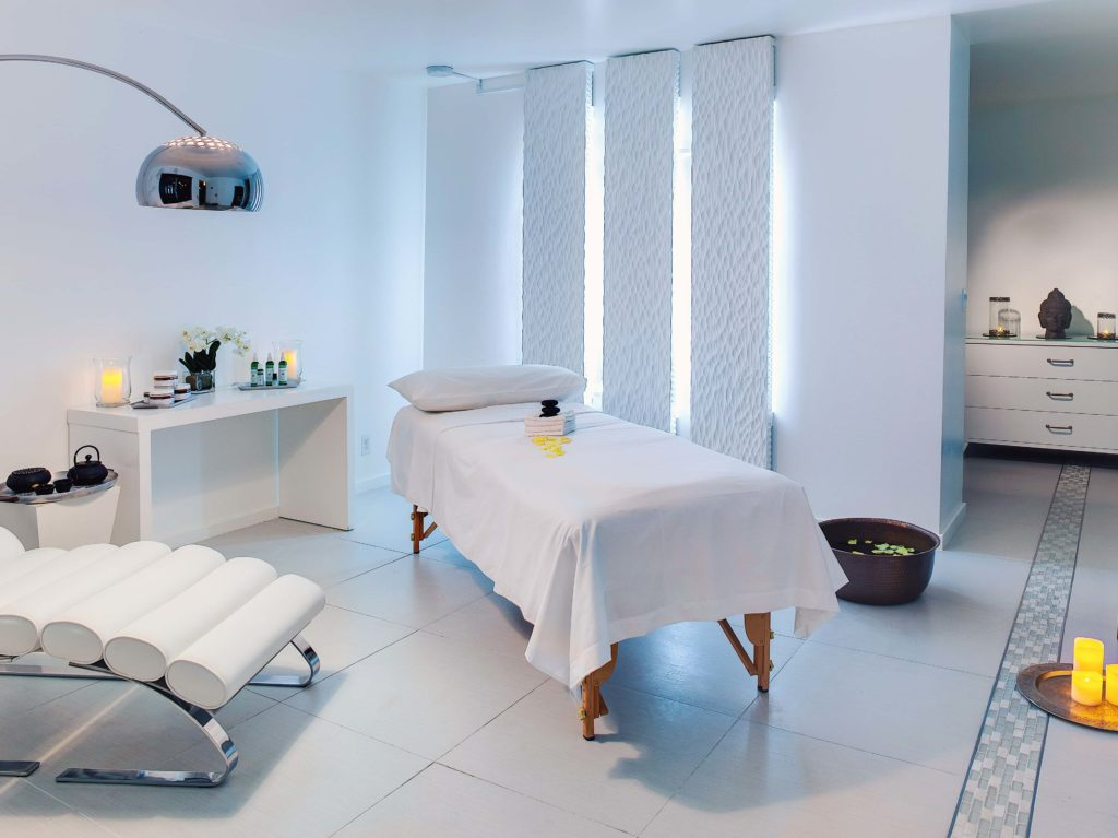 Clean, white spa treatment room with a massage table in the center of room and candle and other spa supplies surrounding the room