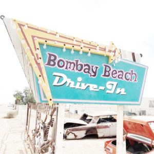 """Teal and purple retro sign reading """"Bombay Beach Drive-In"""" with a yellow and red arrow pointing left, old run down cars in the background"""