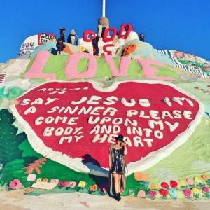 Stylish blonde woman posing in front of Salvation Mountain