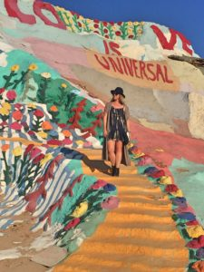Stylish young woman looking off into the distance while standing on shallow, orange stairs at Salvation Mountain
