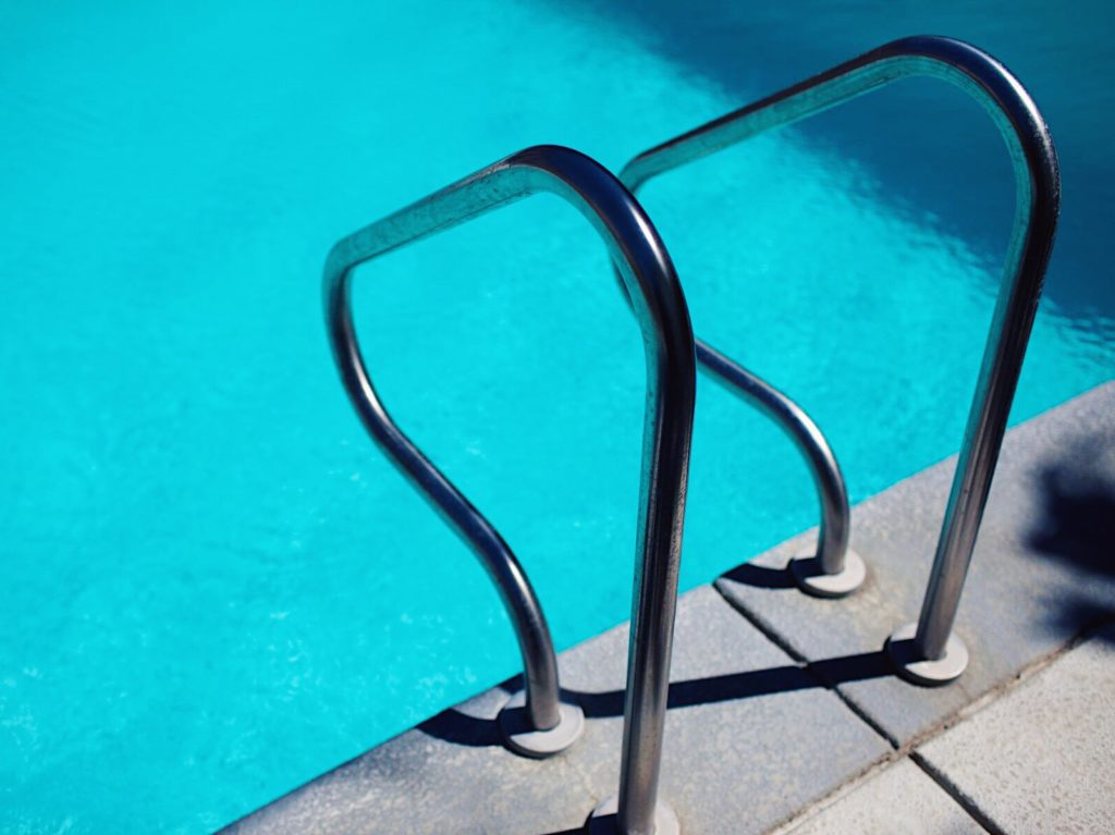 Silver pool handles leading into aqua blue pool water