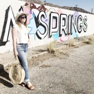 Young blonde woman in light washed jeans and short sleeved white shirt with sunglasses, a hat, brown sandals, and a large woven bag standing in front of a graffitied wall with the San Jacinto mountains peaking out from behind