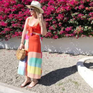 Blonde woman dressed in a colorful, block-colored dress styled with white sandals, white sunglasses, light-colored hat, and small bamboo clutch standing in the sunshine in front of large bougainvillea bushes smiling