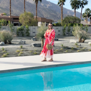 Blonde woman wearing a pink and white floor-length caftan, sunglasses, and sandals carry a small bamboo clutch smiling and walking in front of a pool in Palm Springs with palm trees and the San Jacinto mountains in the background