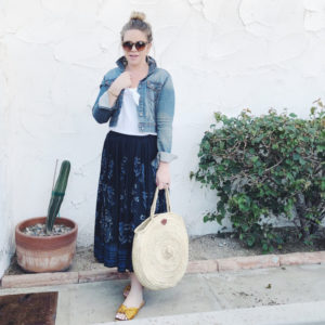 Young blonde woman in a navy maxi skirt, white tee, and denim jacket wear sunglasses, mustard-colored sandals, and a large woven handbag standing in front of a white stucco wall