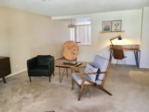 Living room of Chez Jardin #1 showing 2 mid-century modern styled chairs, and desk.