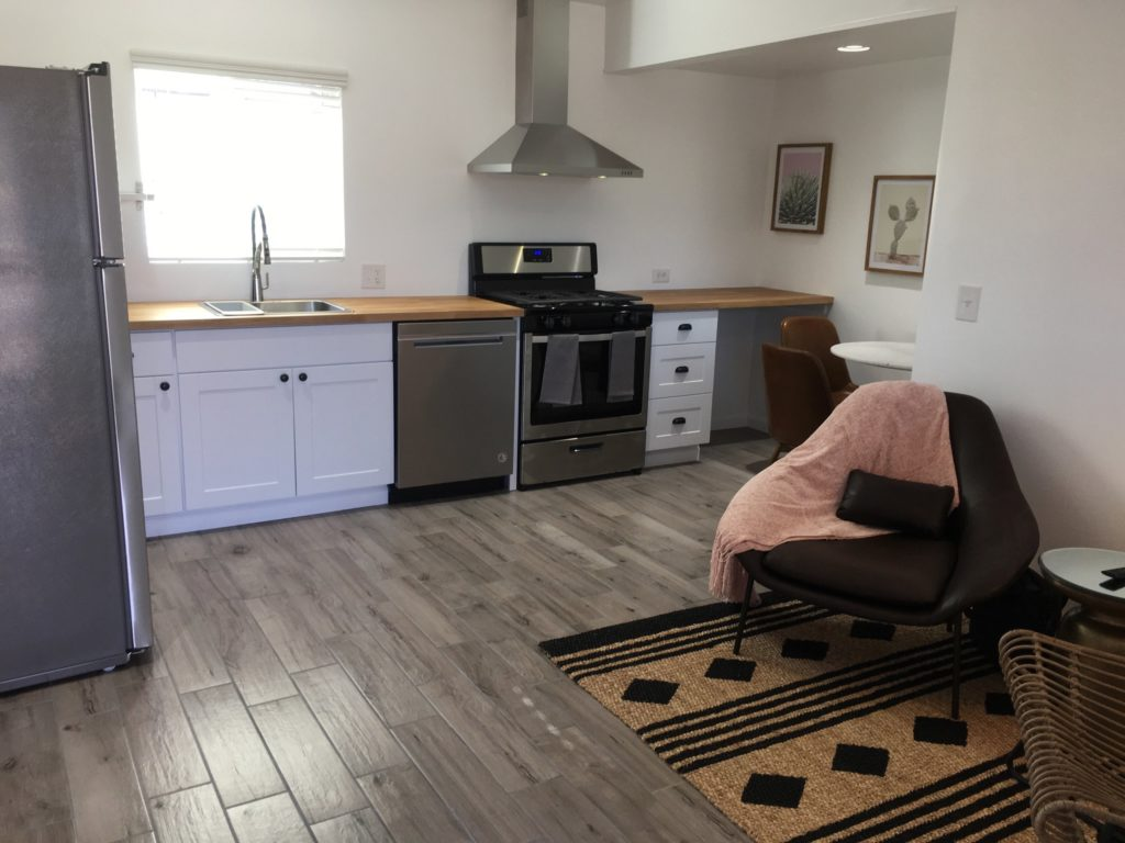 Well appointed kitchen shown with stainless steel appliances, a refrigerator to the left and chair on the right located in the living room of this apartment.
