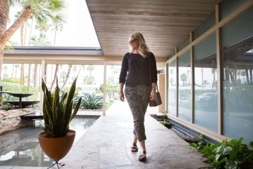 Stylish woman walking through min-century modern styled walkway