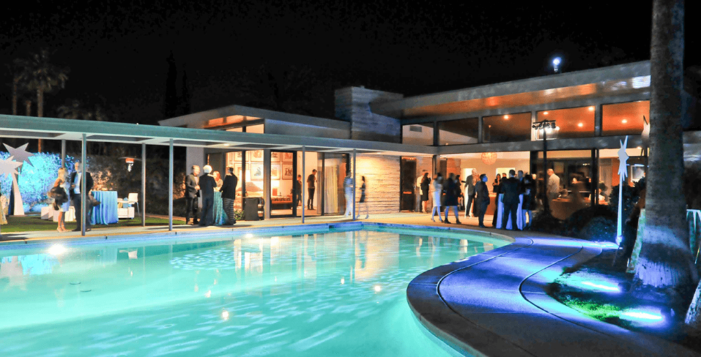 An evening backyard party in Palm Springs. Formerly dressed guests standing around pool