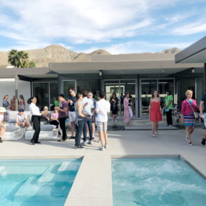 Backyard Palm Spring party with guests standing and lounging around pool