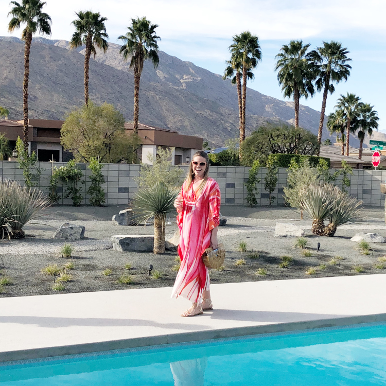 Young blonde woman walking along side swimming pool wearing a pink caftan