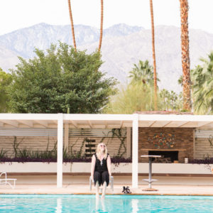 Blonde woman in black, sleeveless jumpsuit laughing and sitting at swimming pool's edge