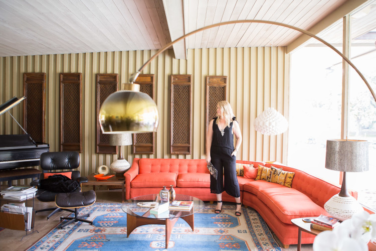 Blonde woman in black, sleeveless jumpsuit with black high heels in mid-century mid-century modern styled living room