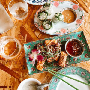 Lovely flat lay of Vietnamese food, spring rolls and egg rolls on a plywood table top