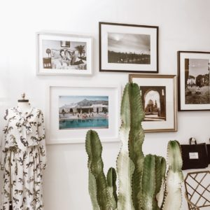 Interior pf Elizabeth & Price displaying a dress, a cactus, and handbags in from of a gallery wall