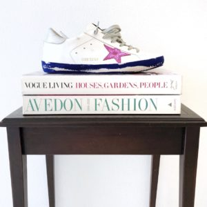 A pair of Golden Goose Deluxe Brand shoes onto of a stack of books