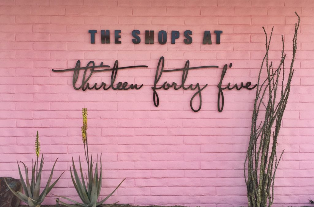 "A pink painted brick wall with ""The Shops at Thirteen Forty Five"""