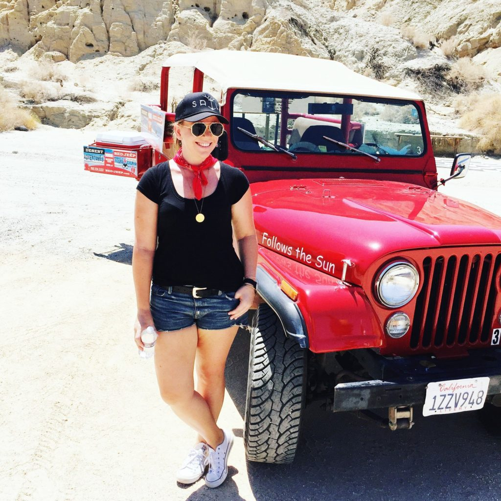 Young blonde woman posing in front of red Jeep
